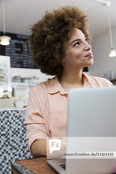 Smiling young woman with laptop in a cafe looking up