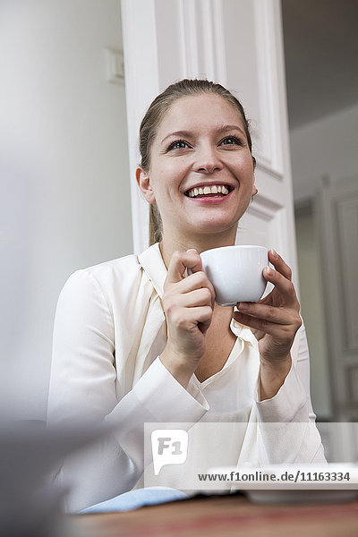 Lächelnde junge Frau mit einer Tasse Kaffee