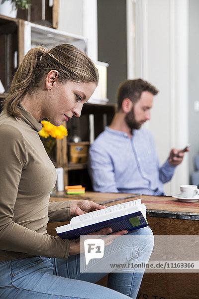 Junge Frau beim Lesen eines Buches mit Mann im Hintergrund
