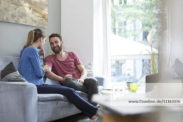 Lächelndes junges Paar auf der Couch sitzend