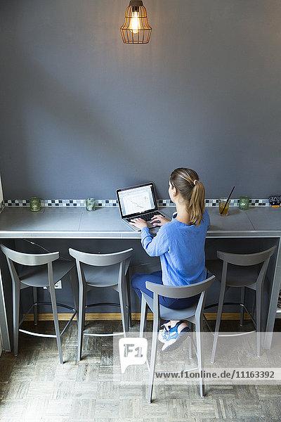 Junge Frau sitzt auf Barhocker mit Laptop