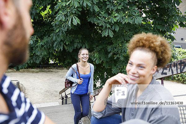 Lächelnde junge Frau geht im Park mit Mann und Frau im Vordergrund die Treppe hinauf
