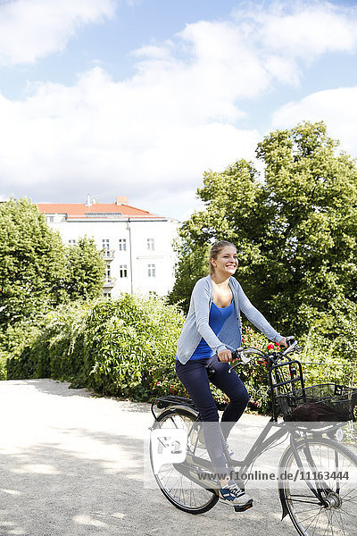 Young woman riding bicycle in park
