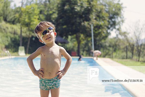 Porträt eines kleinen Jungen mit Sonnenbrille vor dem Schwimmbad Porträt eines kleinen Jungen mit Sonnenbrille vor dem Schwimmbad