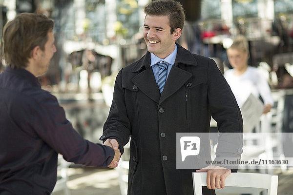 Two businessmen shaking hands at outside restaurant