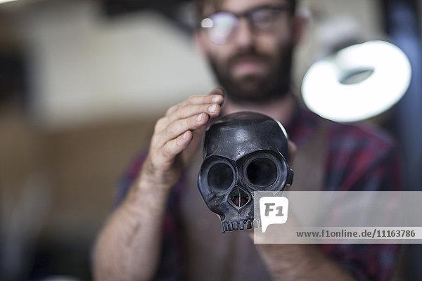 Artist holding skull sculpture