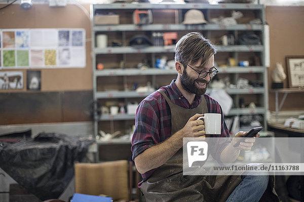 Mann mit Handy bei Kaffeepause in der Werkstatt