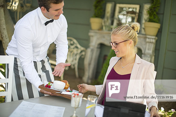 Kellnerin serviert Dessert für Geschäftsfrau bei der Außenrestauration