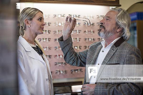 Optiker hilft Kunden bei der Auswahl neuer Brillen