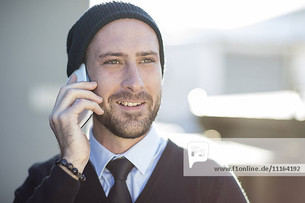 Young man wearing beanie talking on cell phone