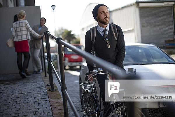 Mann schiebt Fahrrad auf der Stadtstraße