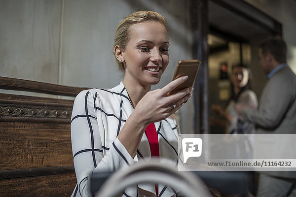 Woman on bench looking at cell phone