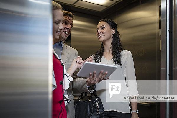 Geschäftsleute im Aufzug mit Tablettengespräch