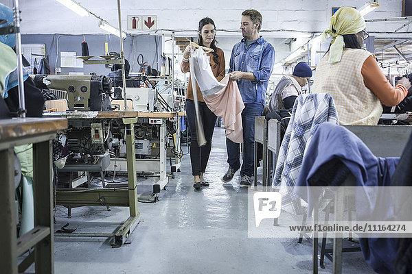 Designer in der Fabrik diskutieren über Kleidung
