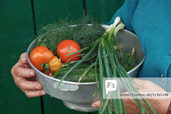 Caucasian woman holding bowl of fresh vegetables