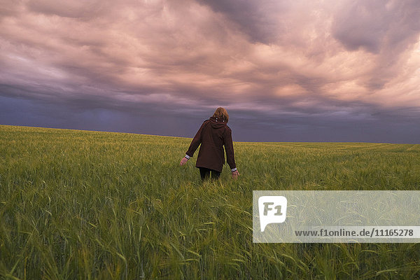 Storm clouds over Caucasian woman walking in field of tall grass