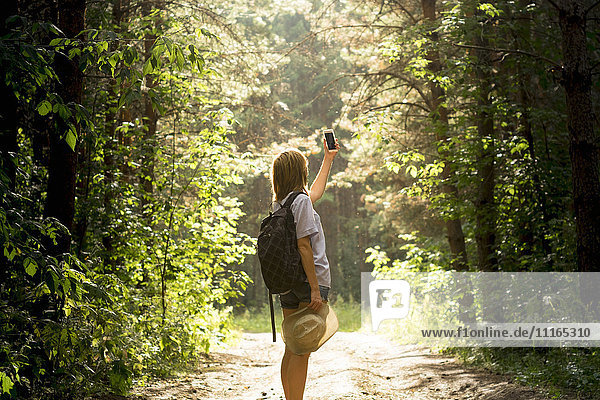 Caucasian woman photographing forest trees with cell phone