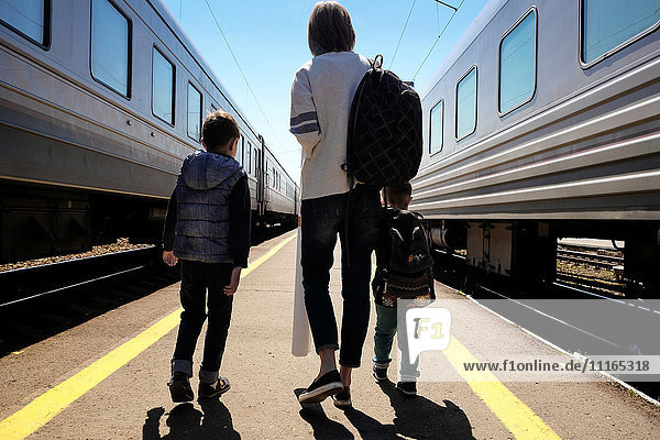 Mother and sons walking between trains at train station