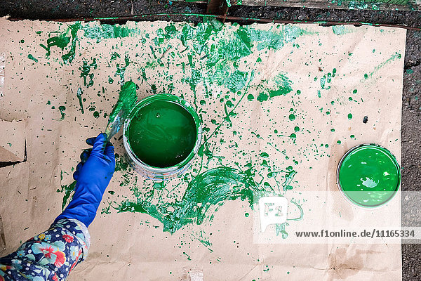 Hand of Caucasian woman splashing green paint on paper