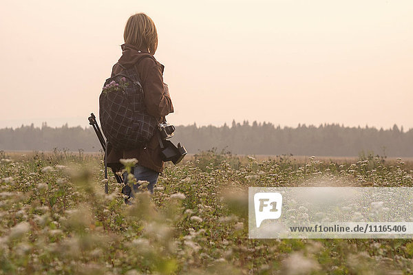 Caucasian photographer standing in field of flowers