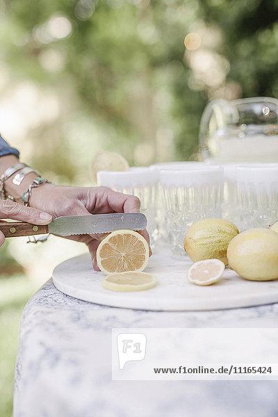 Nahaufnahme einer Frau  die an einem Tisch in einem Garten steht und für ein Getränk Zitronen in Scheiben schneidet. Nahaufnahme einer Frau, die an einem Tisch in einem Garten steht und für ein Getränk Zitronen in Scheiben schneidet.