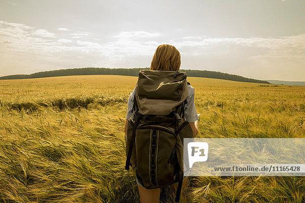 Caucasian woman walking in field carrying backpack