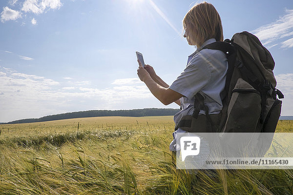 Caucasian woman standing in field using cell phone