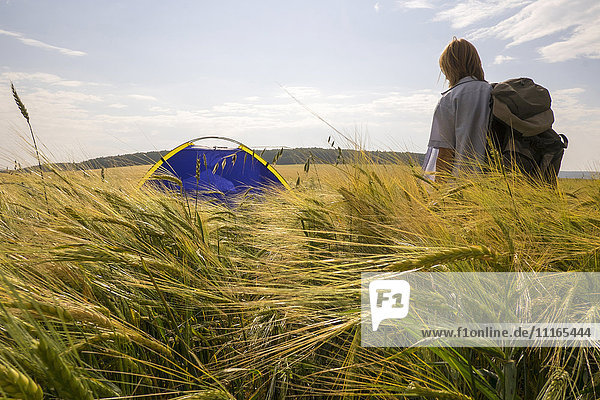 Caucasian woman standing in field near camping tent