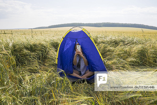 Caucasian women sitting in tent taking cell phone selfie