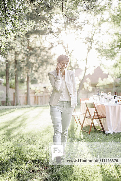 Woman standing in a sunlit garden  talking on her mobile phone.