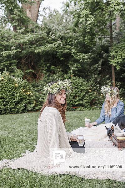 Zwei lächelnde Frauen mit Blumenkränzen im Haar sitzen in einem Garten.