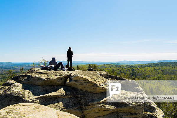 Caucasian friends sitting on mountain rock admiring scenic view