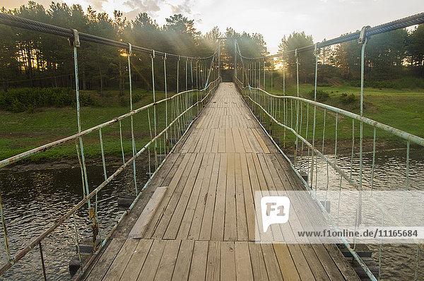 Sunbeams on wooden footbridge over river