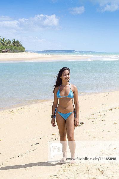 Mixed Race girl standing on beach