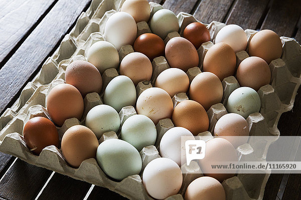 A tray of fresh organic eggs  in a variety of colours.