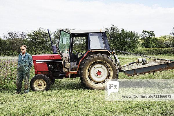 Ein stehender roter Traktor und ein an die Motorhaube gelehnter Fahrer auf einem Feld im Sommer.
