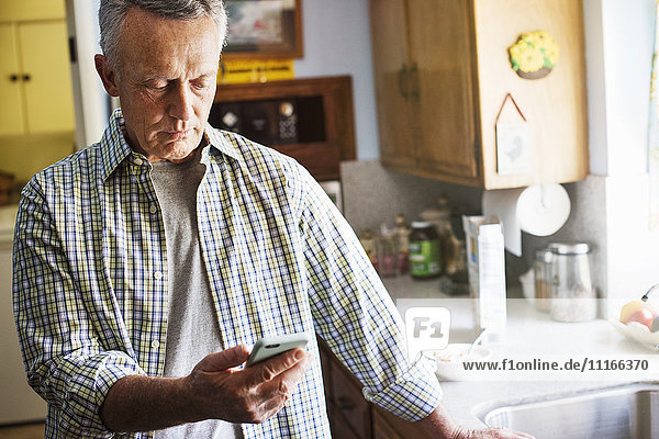 Senior man standing in a kitchen  using a mobile phone.
