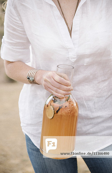 Close up of a woman holding a large glass bottle with a drink.