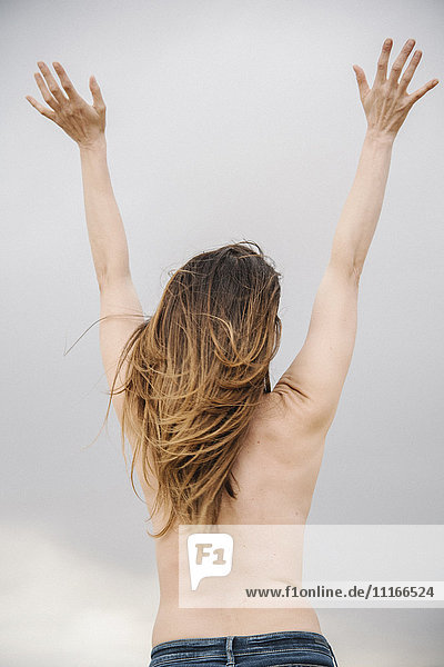 Rear view of a topless woman standing with her arms raised. Cloudy sky.