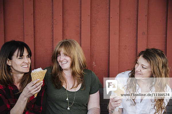 Three women sitting on a bench  eating ice cream.