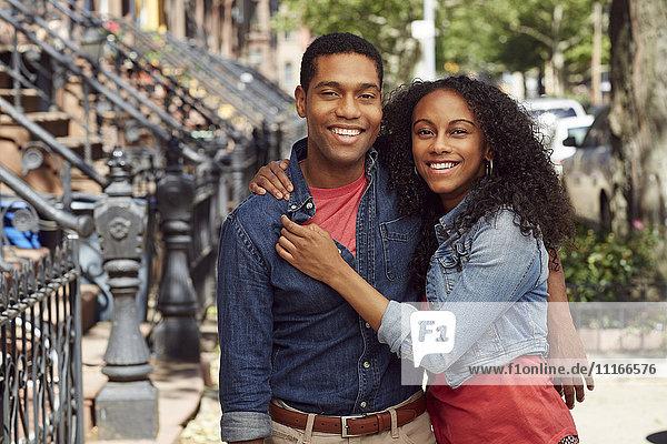 Smiling couple hugging on city sidewalk