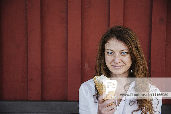 Woman with long brown hair sitting on a bench  eating ice cream.