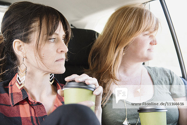 Two women in a car holding coffee cups.