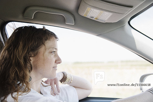 Woman in a car on a road trip  in the driving seat  elbow on the door.
