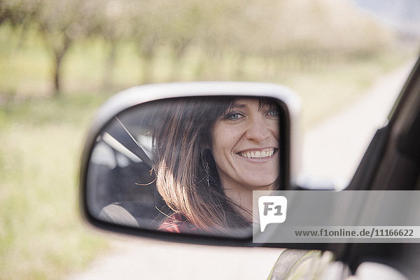 Woman in a car  smiling at her reflection in the side mirror.