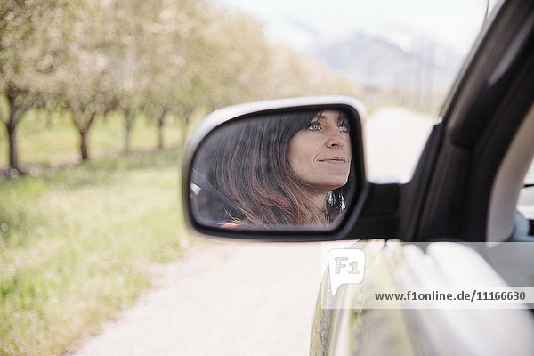 Woman in a car on a road trip  reflection seen in the side mirror.