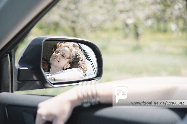 Woman in a car on a road trip  looking out of window  reflection in the side mirror.