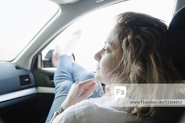 Woman in a car on a road trip  her legs and bare feet out of the window.