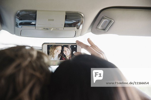 Two women in a car on a road trip taking a selfie.