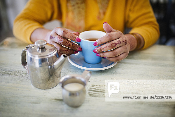 Woman with henna tattoo on hands drinking tea